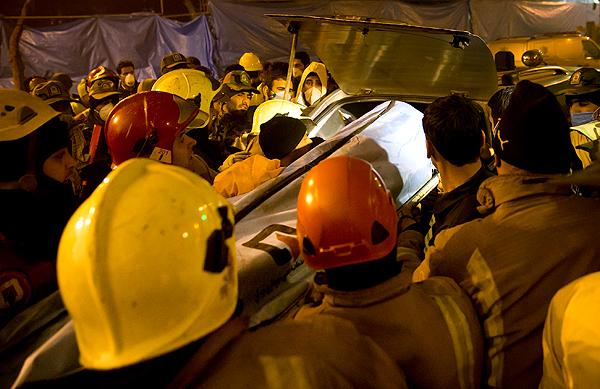 تصاویر/ لحظه بیرون کشیدن پیکر آتش نشان از زیر آوار پلاسکو