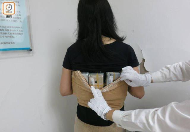 (عکس) زنی که ۵۰ آیفون را در لباسش جاسازی کرد