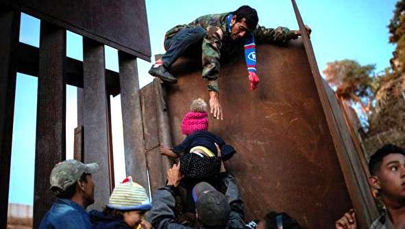(تصاویر) عبور شبانه مهاجران از حصار مرزی مکزیک و آمریکا