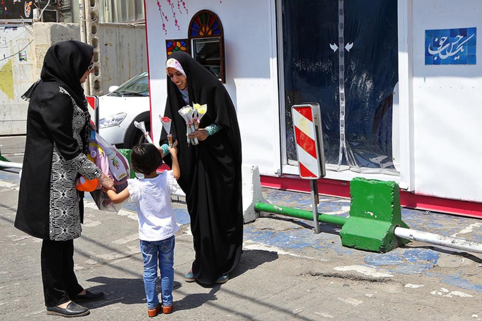 اهدای گل و کتاب مخصوص کودکان به رهگذران در غرفه یک حس خوب در میدان صادقیه