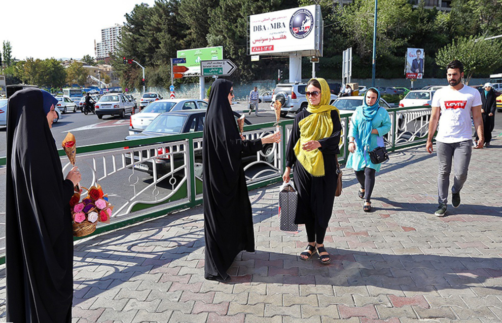 اهدای گل به رهگذران توسط مسئولین غرفه یک حس خوب در میدان صنعت تهران