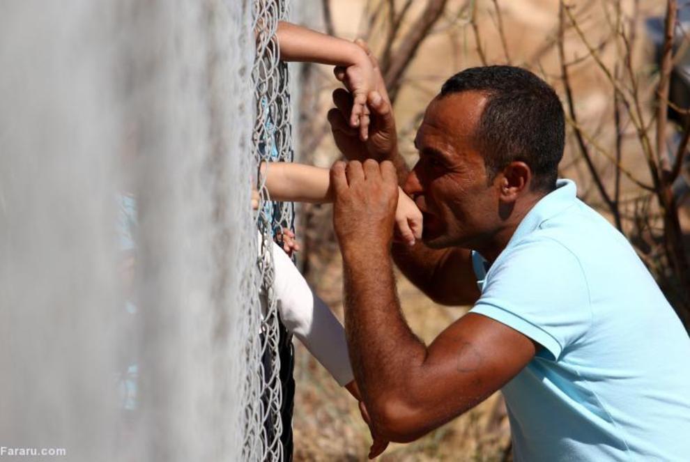 مرد پناهنده سوری در حال ملاقات فرزندش در کمپ آوارگان سوری