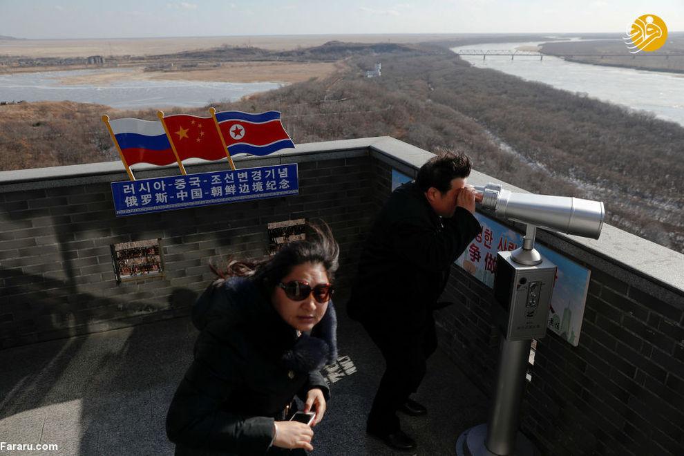 گردشگران در مرز کره شمالی و چین کره شمالی را تماشا میکنند
