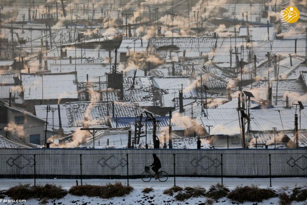 مردی سوار بر دوچرخه در خاک کره شمالی در مرز چین