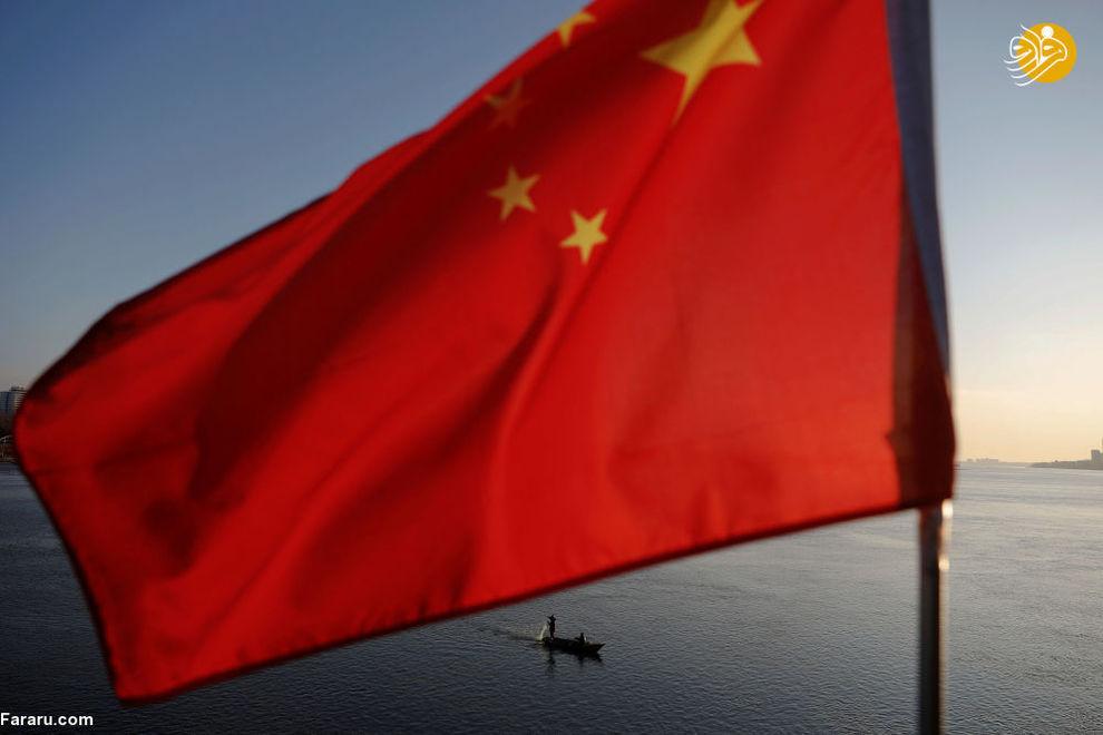 ماهیگیر کره شمالی در زیر پرچم چین در رودخانه یالو در مرز چین و کره شمالی