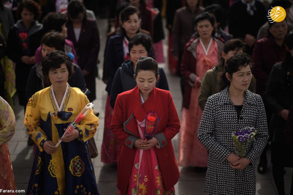 نثار گل به پای مجسمه رهبر کره شمالی در پیونگ یانگ در زمان جشن خورشید