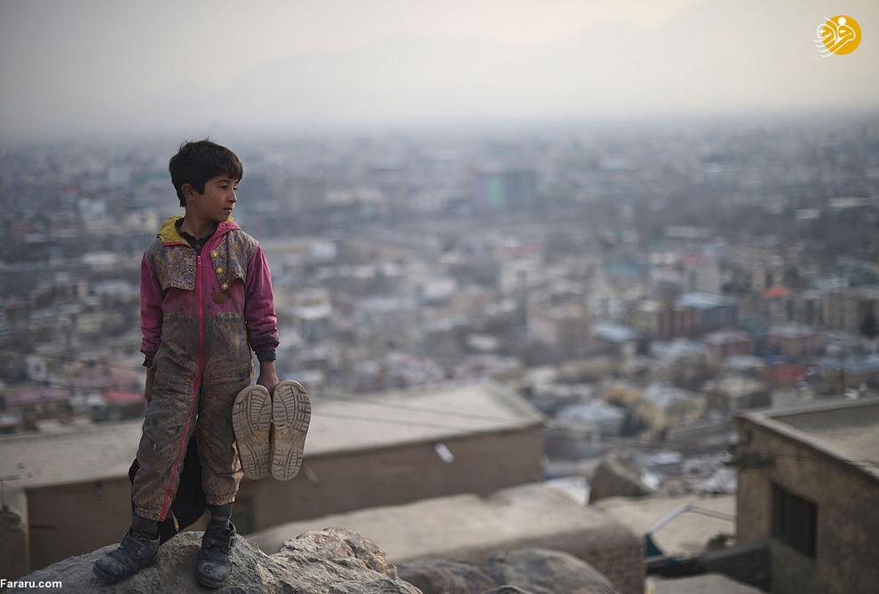 نمایی از سامی الله پسر 11 ساله افغانستانی پشت به گورستان کابل. سامی الله دومین پسر خانواده هشت نفره و تنها نان آور خانه است. او از طریق واکس زدن امرار معاش میکند. فقر و ناامنی هزاران کودک را به کار کودکان در افغانستان تحمیل کرده است. کودکان از 5 تا 15 به جای حضور در مدارس در خیابان ها کار می کنند و اغلب نان آور خانواده های خود هستند