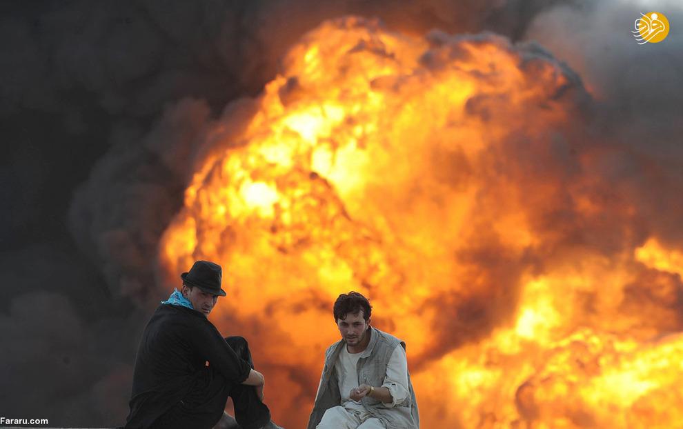 مردان افغان در حال تماشای تانکر در حال سوختن
