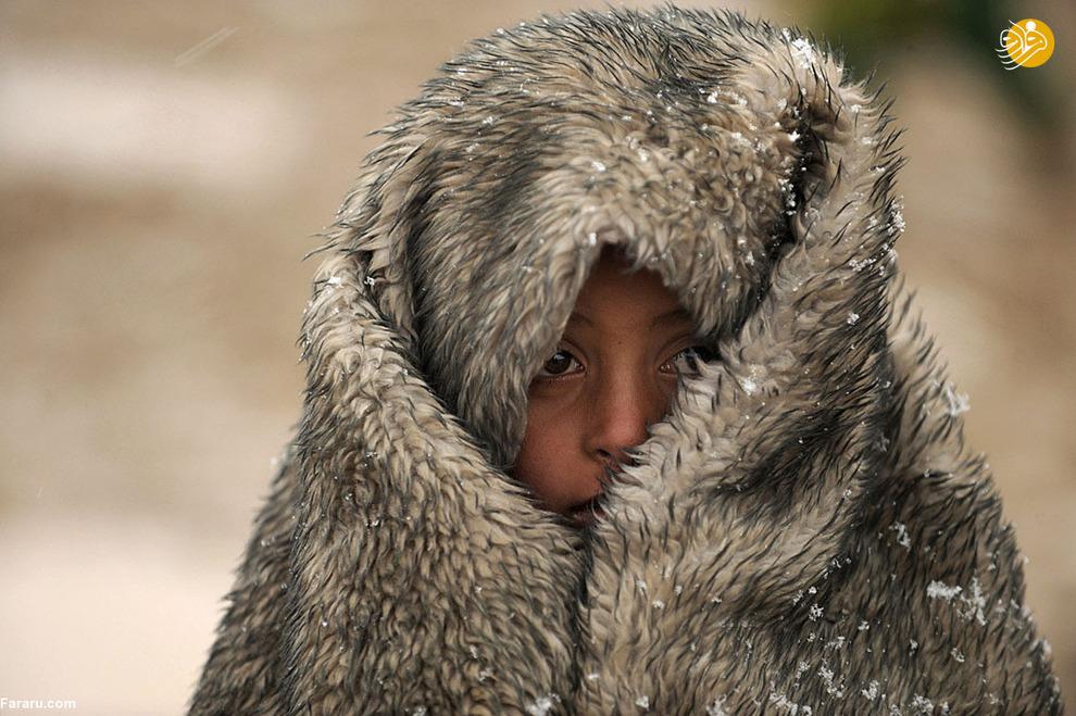 کودک آواره افغان در ولایت هلمند هنگام بارش برف