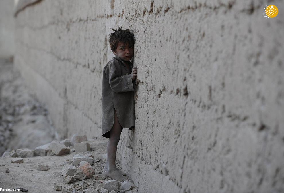 پسر بچه افغان که به دیواری در حومه کابل تکیه کرده است
