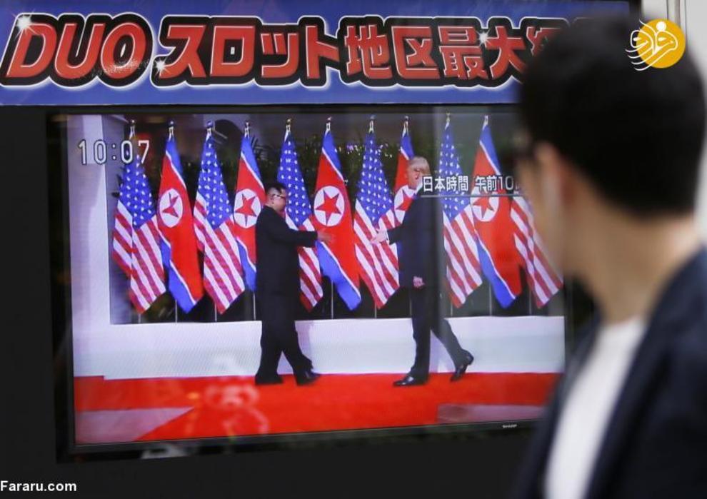 رهگذر ژاپنی در حال نگاه کردن اخبار دیدار ترامپ و اون در توکیو