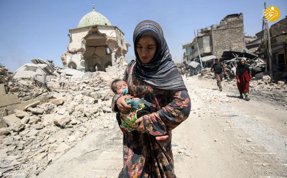 زن عراقی همراه با کودک خود در شهر موصل، عراق