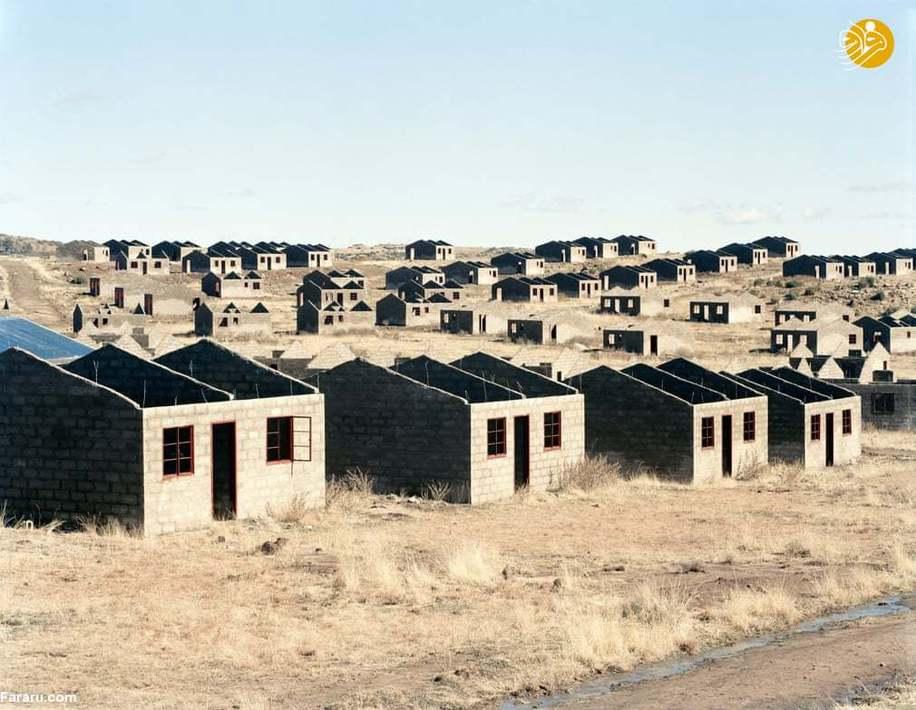 (1998) خانههای ناتمام که بخشی از یک پروژۀ توسعۀ شهری 1000 خانهای راکدشده هستند. تخصیص منابع مالی در سال 1998 انجام شد و ساخت و ساز در سال 2003 آغاز گردید. مسئولین و یکی از سیاستمداران دلایل گوناگونی را برای راکد شدن و توقف طرح مطرح میکنند: کمبود آب، دزدی مصالح، مشکل دفع فاضلاب، مشکلات ناشی از میزان بالای مس در خاک و کمبود بودجه. تا آگوست سال 2006 که این عکس گرفته شده، 420 خانه تکمیل شدهاند.