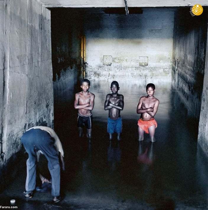 (2002) در حالی که فرناندو آگوستو لوتا لباسهایش را میشوید، آگوستو موکیندا (13 ساله)، زی ژانو (12 ساله)، و زندالا (10 ساله در آبی که از زیر زمین بالا آمده و در یک چاه معدنی در یک معدن قدیمی آزبست وارد شده، ایستادهاند. این آب احتمالاً به آزبست آلوده است.