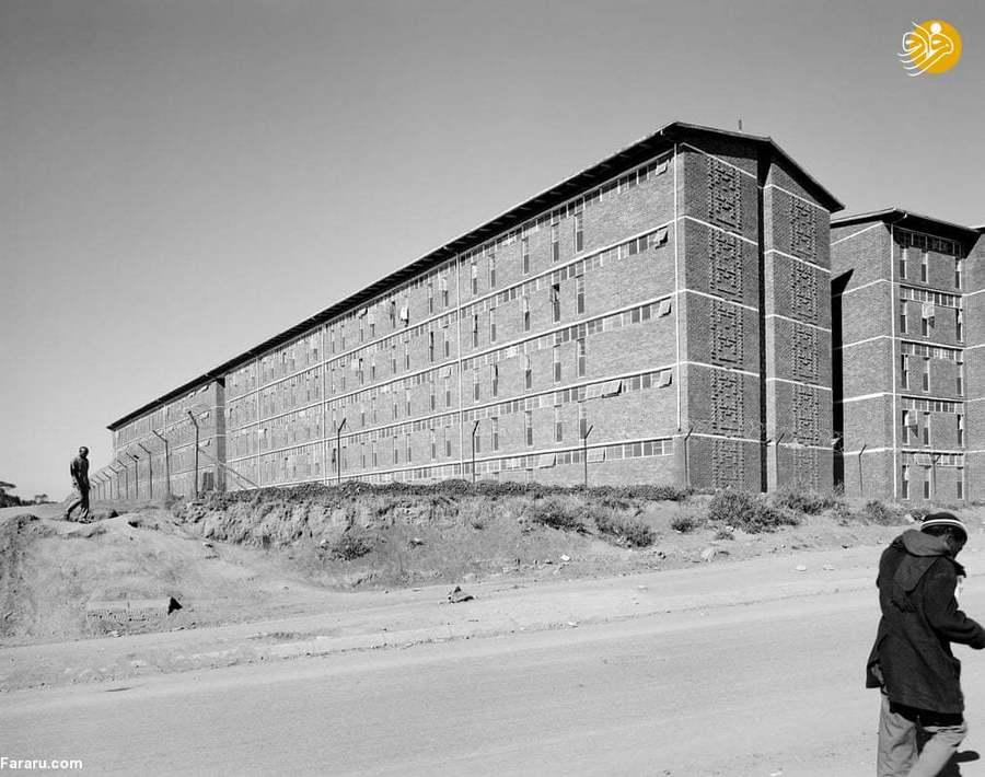 (1988) نمایی از ضلع جنوب شرقی اقامتگاهی که برای کارگران مرد سیاهپوست در دورۀ آپارتاید ساخته شده بود و بخشی از طرحی بود تا شهر یوبورگ و حومهاش را اختصاصاً سفیدپوستنشین کنند.