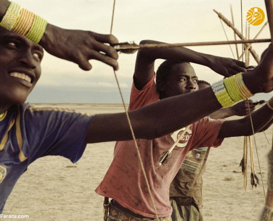 مردان جوان هادزا در حال آزمایش کمان خود برای شکار هستند
