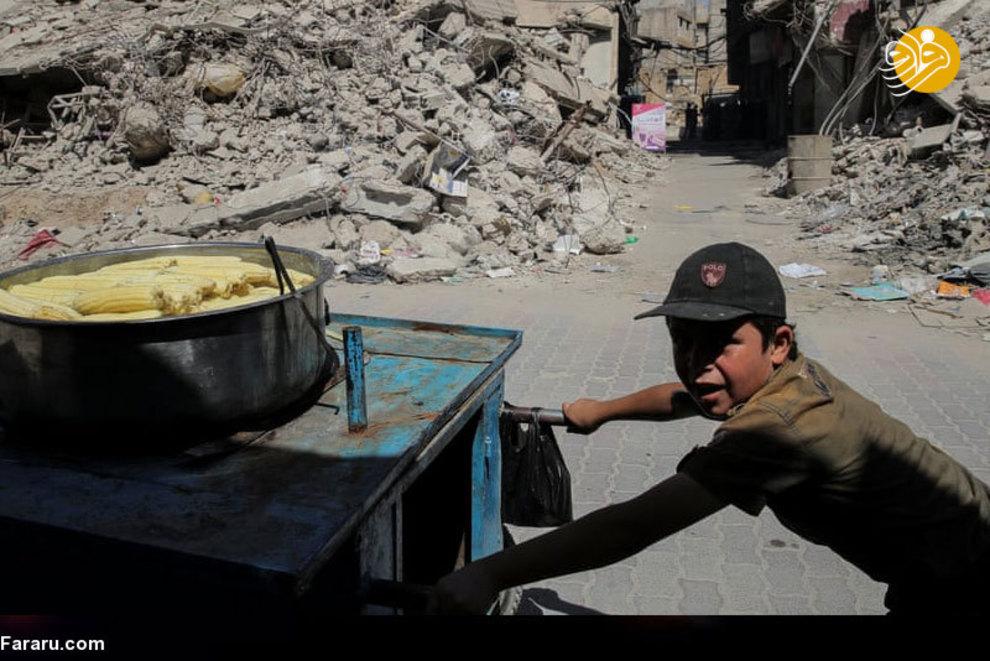 خسارت زیادی در طول بمباران به این منطقه واردشد. تا جایی که مردم  غوطه به سختی کسب درآمد می کنند. در این تصویر تلاش کودکی را می بینید که در حال فروش ذرتهای خود است