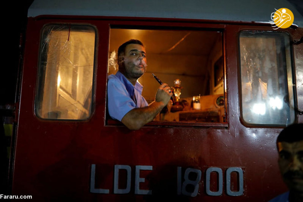راننده قطار در حالی که منتظر مسافران نمایشگاه بین المللی است با کشیدن سیگار خود را مشغول کرده