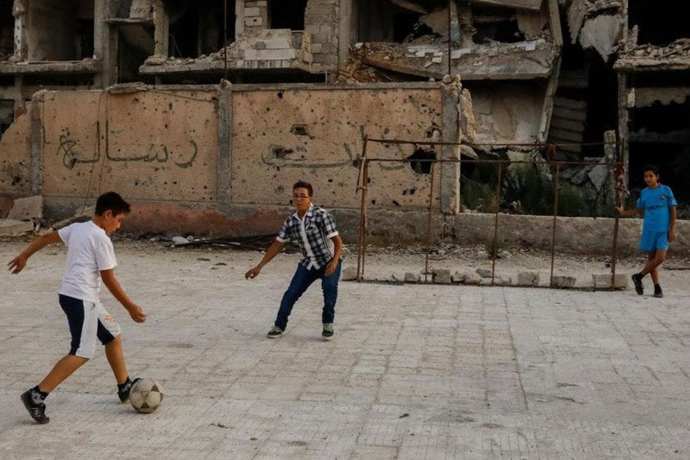 کودکان در منطقه الخالدیه، در بخش حمص بازی فوتبال می کنند