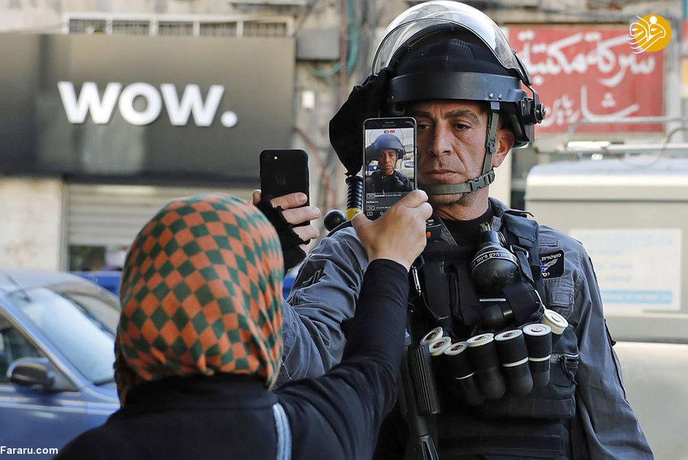 یک زن فلسطینی درمقابل یک سرباز رژیم صهیونیستی، با گوشی همراه خود از او عکس میگیرد که متقابلا سرباز نیز همین کار را انجام میدهد. درگیریهای شدیدی در نوار غزه بین مردم فلسطین و نیروهای رژیم صهیونیستی شکل گرفته است.