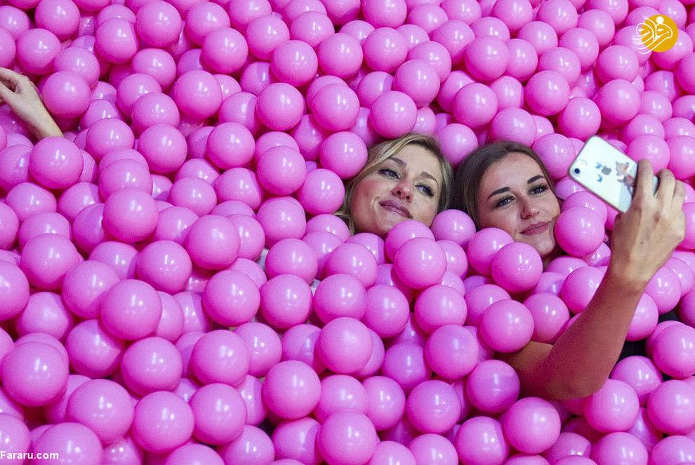 دختران جوان آلمانی در حال سلفی گرفتن در یک استخر پر از توپهای رنگی (کلن : 2018)