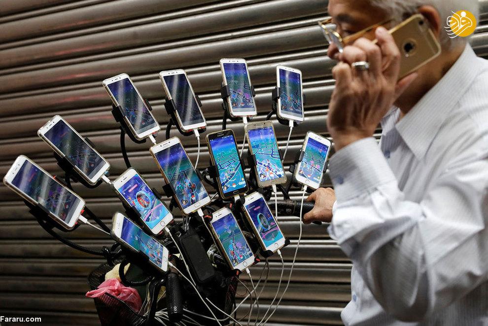 چن سن یوان 70 ساله، معروف به پدربزرگ پوکمون گو. این مرد مسن در حالی که با تلفن حرف می زند همزمان با چند گوشی که بر روی دوچرخه خود نصب کرده، در حال بازی کردن است(تایوان 2018)