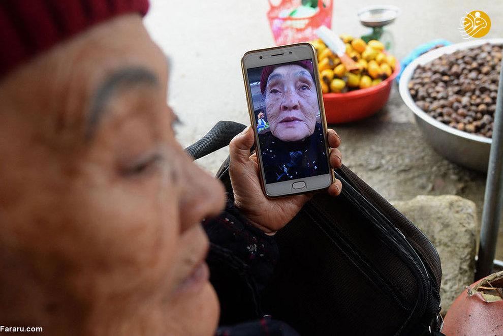 زن دستفروش 75 ساله در حالی که اجناس خود را میفروشد، همزمان با گوشی همراه خود سلفی می گیرد.