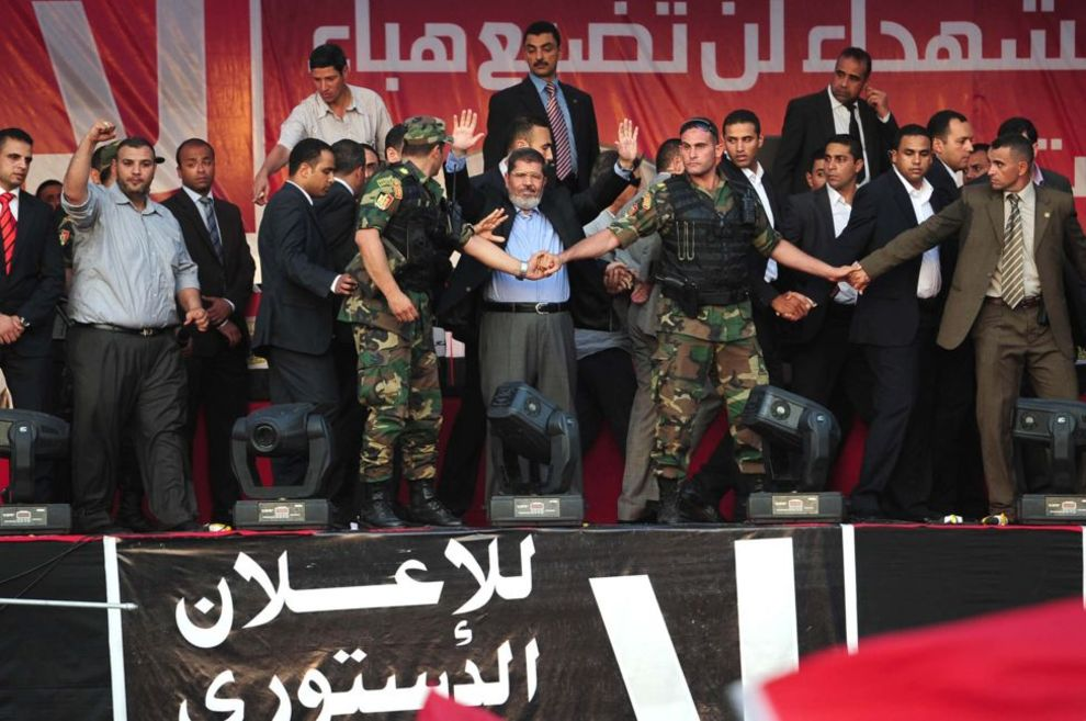 محمد مرسی، رئیس جمهور منتخب مصر در میان حلقه محافظانش در حال ادای سوگند غیر رسمی ریاست جمهوری. دهها هزار نفر از هواداران آقای مرسی در میدان تحریر قاهره در مخالفت با فرماندهان ارتش که میخواستند قدرت او را محدود کنند، تظاهرات کردند. آقای مرسی یک روز بعد به جای پارلمان مصر در دادگاه قانون اساسی سوگند رسمی یاد کرد - قاهره، ۲۲ ژوئن ۲۰۱۲.