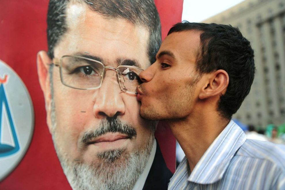 یک هوادار محمد مرسی در جریان جشنهای پیروزی آقای مرسی در انتخابات تصویر او را میبوسد. محمد مرسی روز یکشنبه بعد ازانتخابات اعلام پیروزی کرد تا اولین رئیس جمهور مصر باشد که در یک انتخابات دموکراتیک انتخاب میشود - مصر، ۲۴ ژوئن ۲۰۱۲.