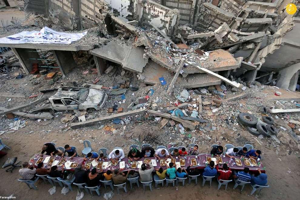 مراسم افطار گروهی از فلسطینیان در کنار ساختمان های تخریب شده بر اثر حملات هوایی اسرائیل در غزه