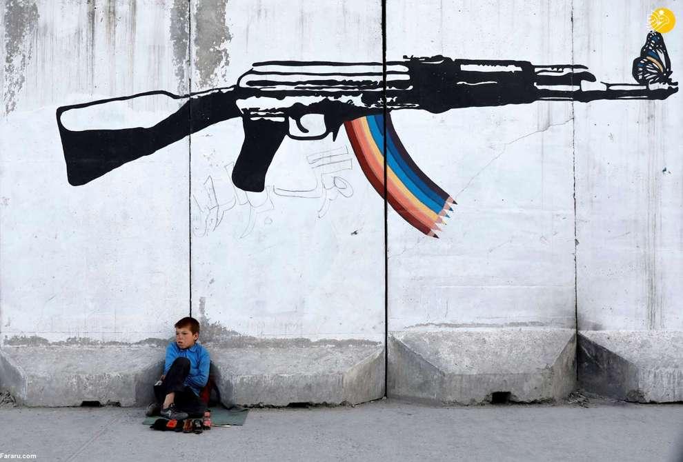 کودک کفاش نشسته زیر یک نقاشی دیواری در کابل